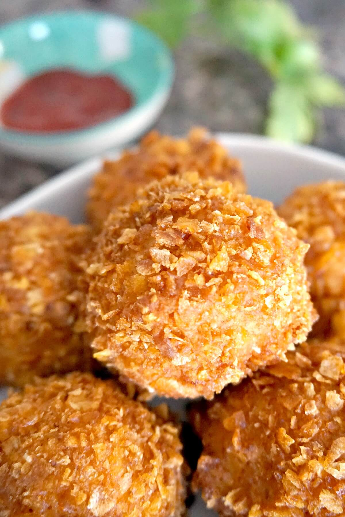 Popcorn chicken balls in a bowl with a small bowl with ketchup in the background
