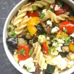 Overhead shoot of a white bowl with roasted vegetable pasta salad and feta