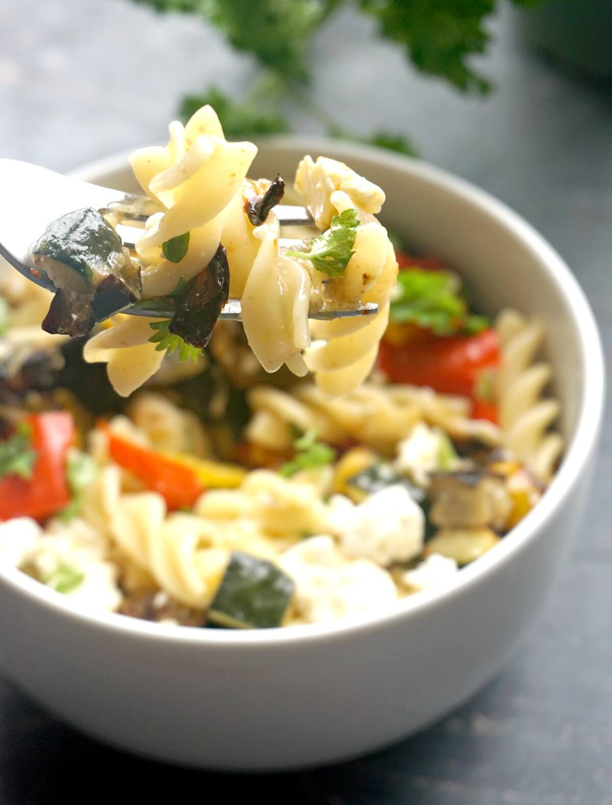 A white bowl with pasta salad that has veggies and feta in