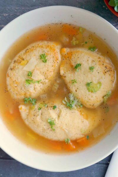 Overhead shoot of a white bowl of semolina dumpling soup