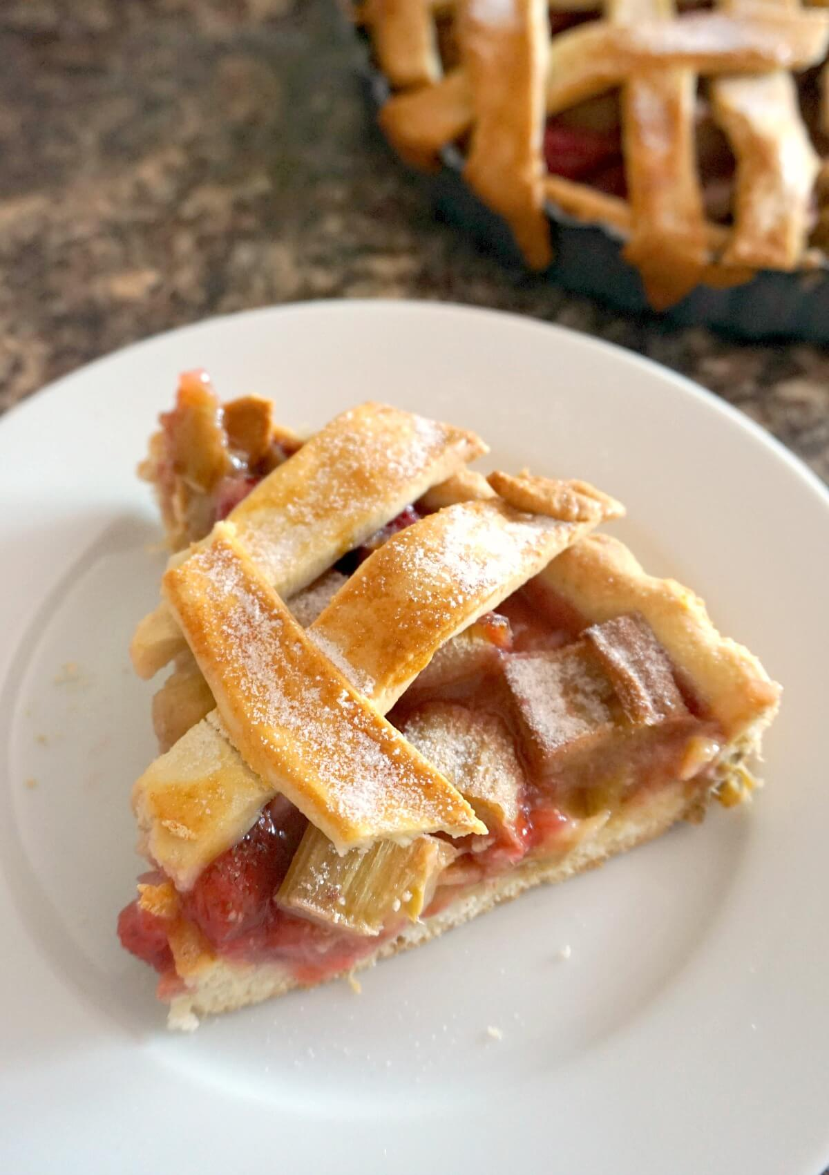 A white plate with a slice of strawberry and rhubarb pie