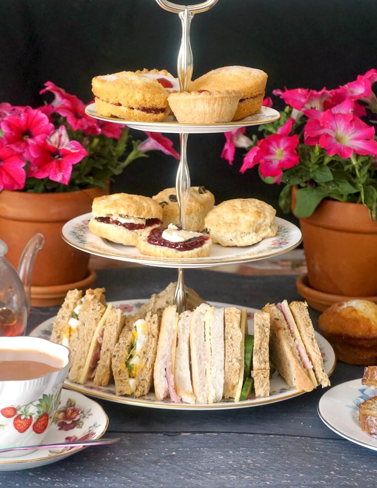 A cake stand with afternoon tea treats, a cup of tea and flowers in the background