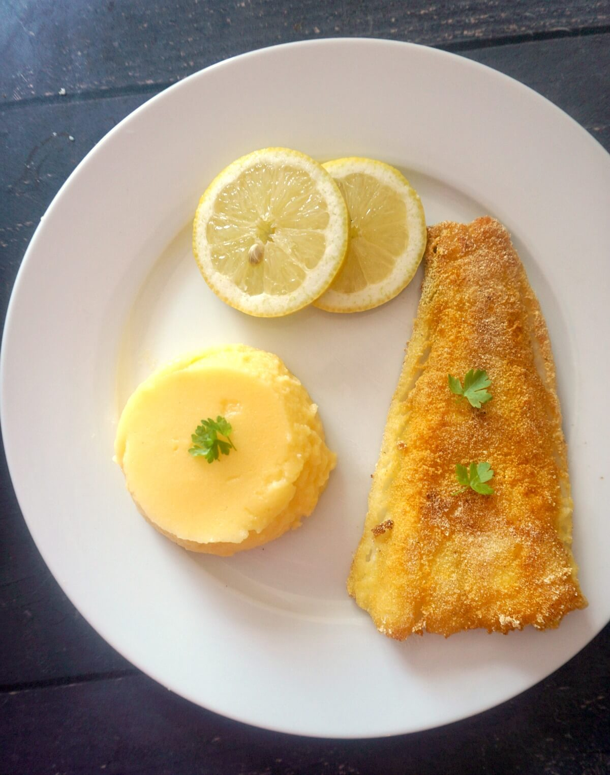 A white plate with a fried fish fillet, 2 slices of lemon and polenta