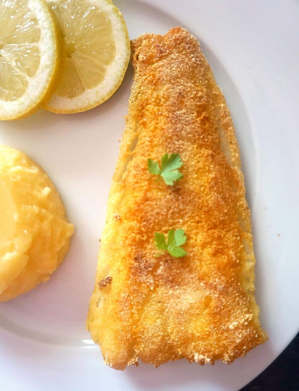 Overhead shoot of a fried fish fillet on a white plate with 2 slices of lemon and polenta