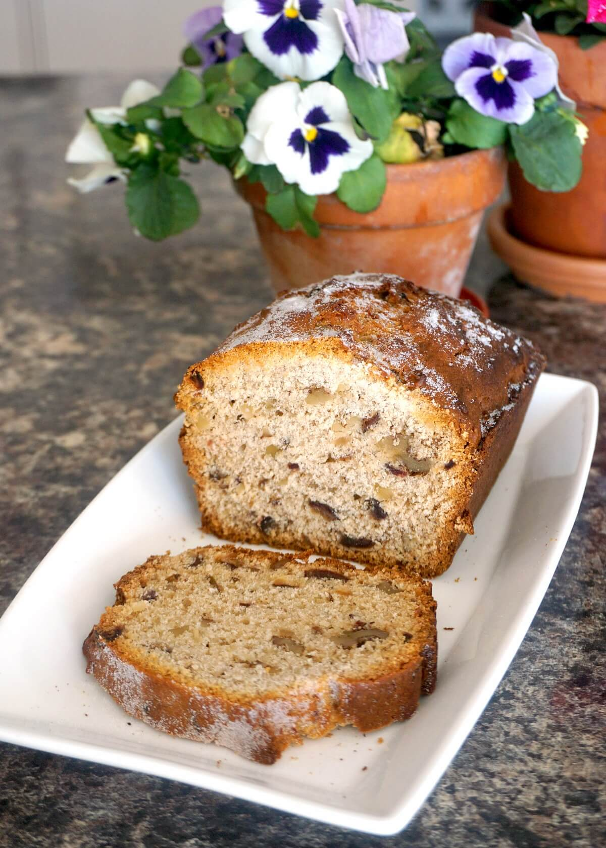 A sliced walnut and date cake on a rectangle white plate with a flower pot in the background