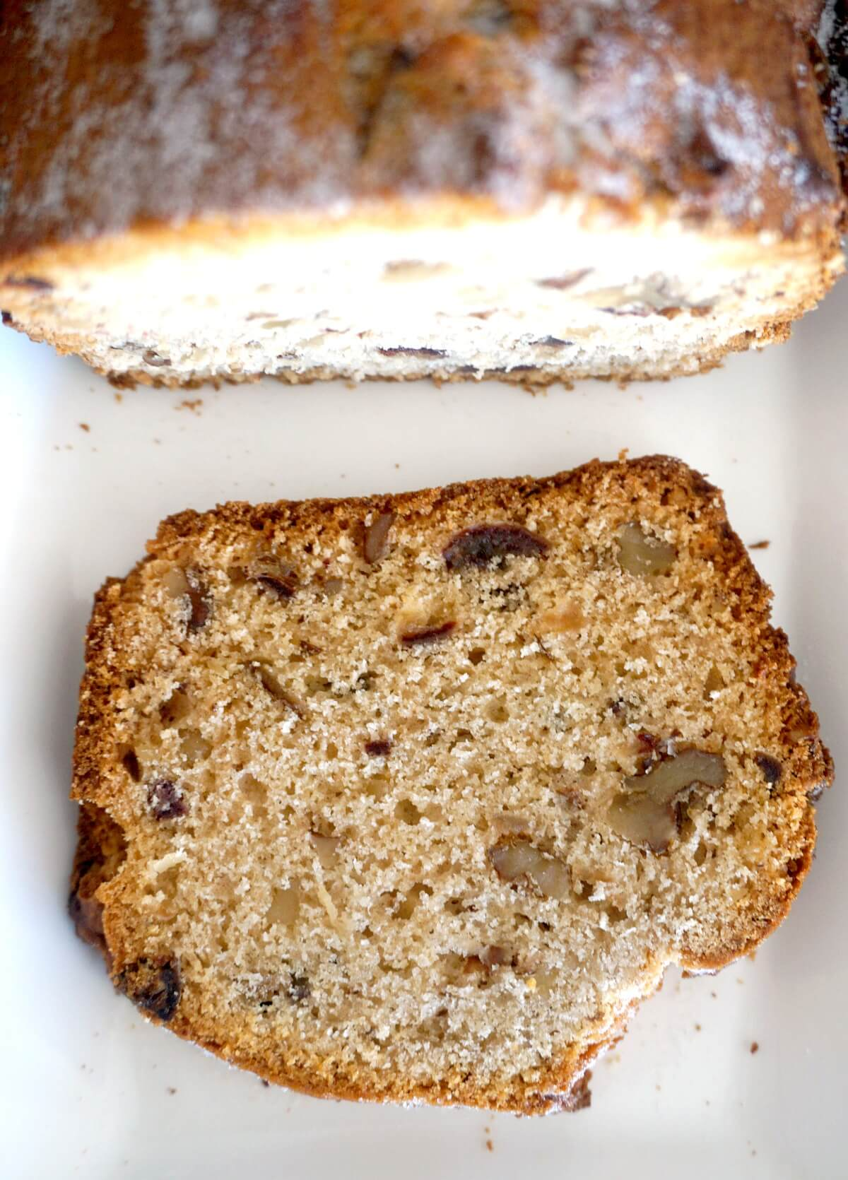 Overhead shoot of a slice of walnut and date loaf on a white plate