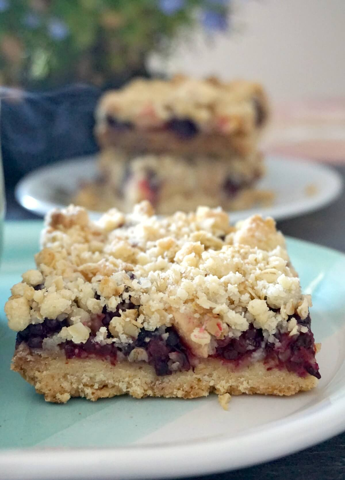 A slice of apple and blackberry crumble bar on a light blue plate