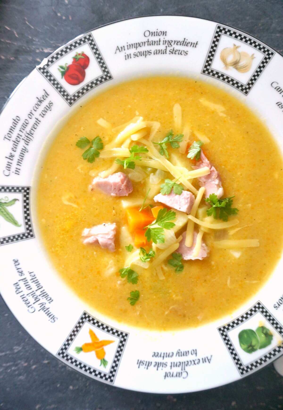 Overhead shoot of a plate with creamy soup garnished with ham and veggie chunks and grated cheese