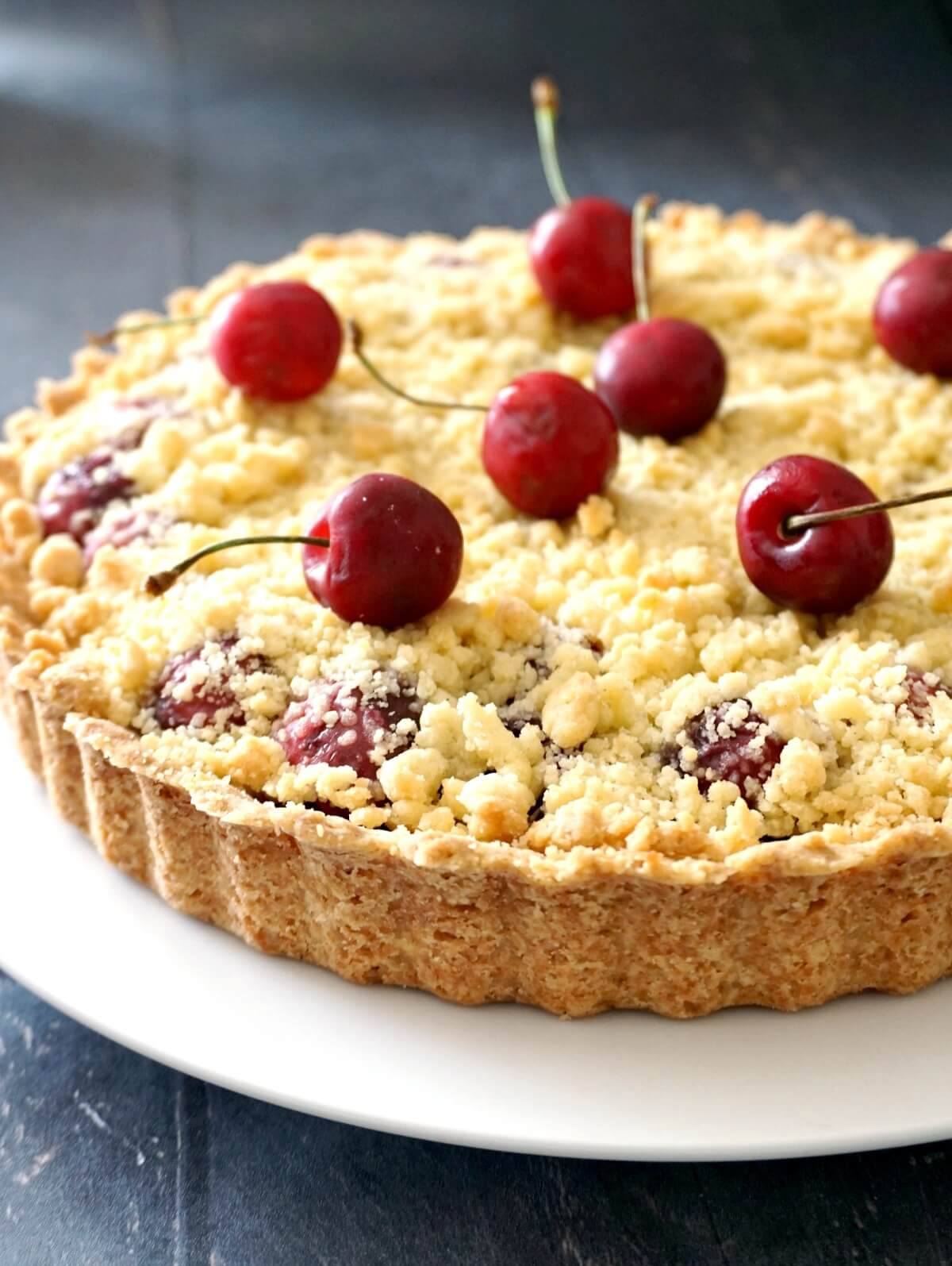 A pie on a white plate with cherries on top