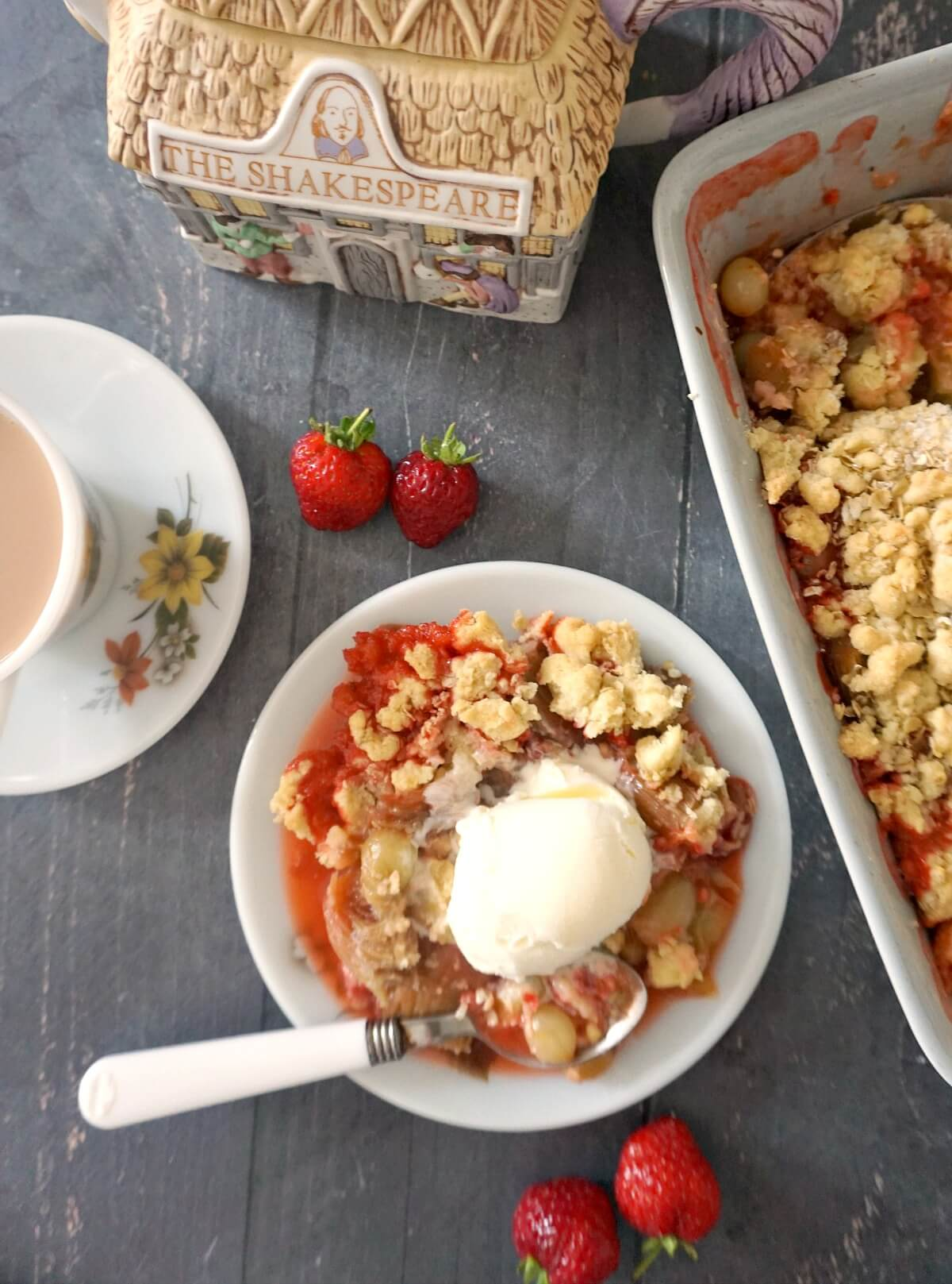 Overhead shoot of a white plate with fruit crumble, a cup of tea on a saucer, a tea pot, strawberries and a dish with crumble