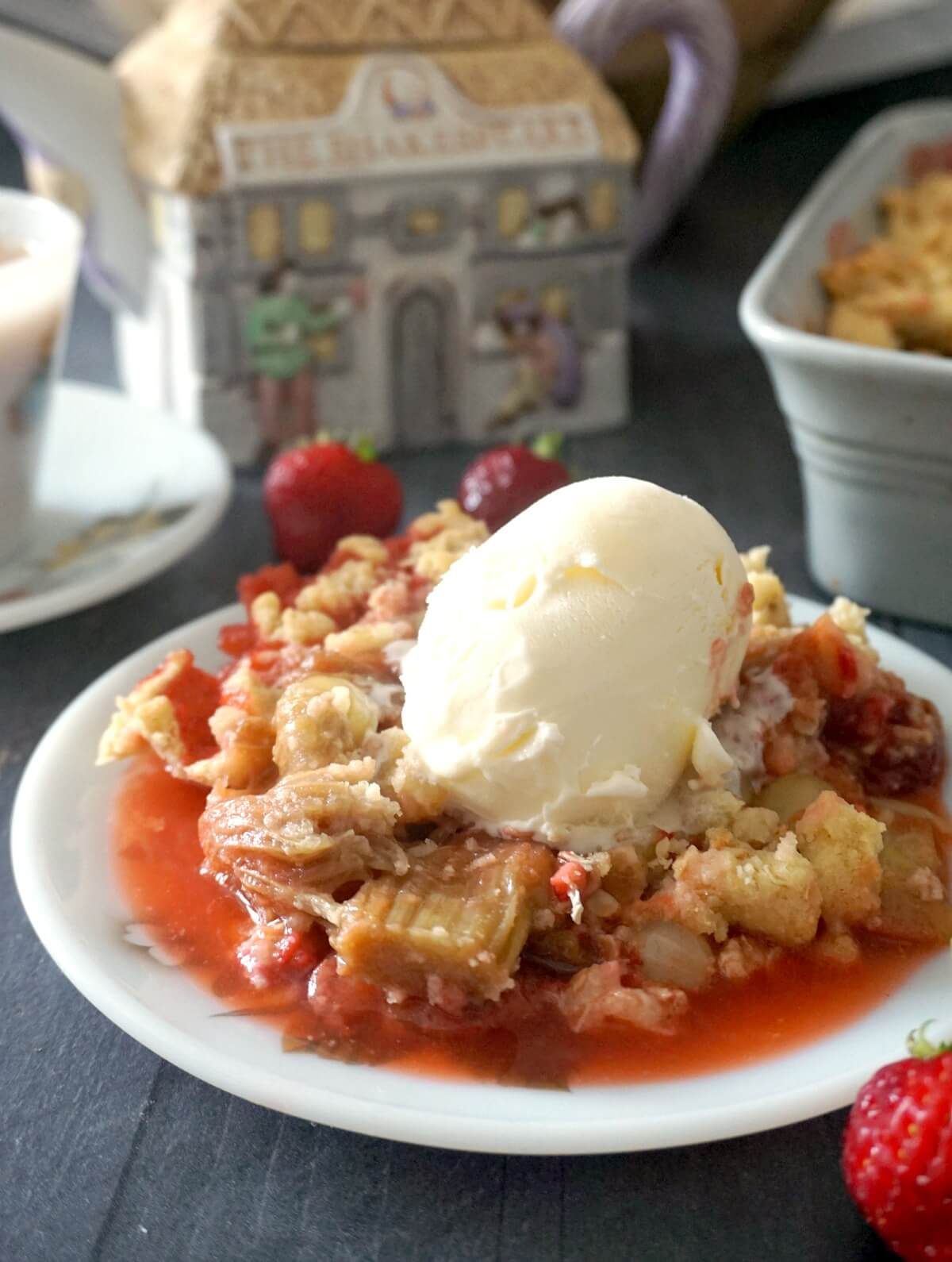 A white plate with fruit crumble topped with a scoop of ice cream