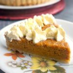 A slice of cream-decorated sweet potato pie