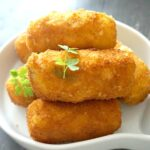 A white plate with 5 potato croquettes and 2 parsley leaves on top