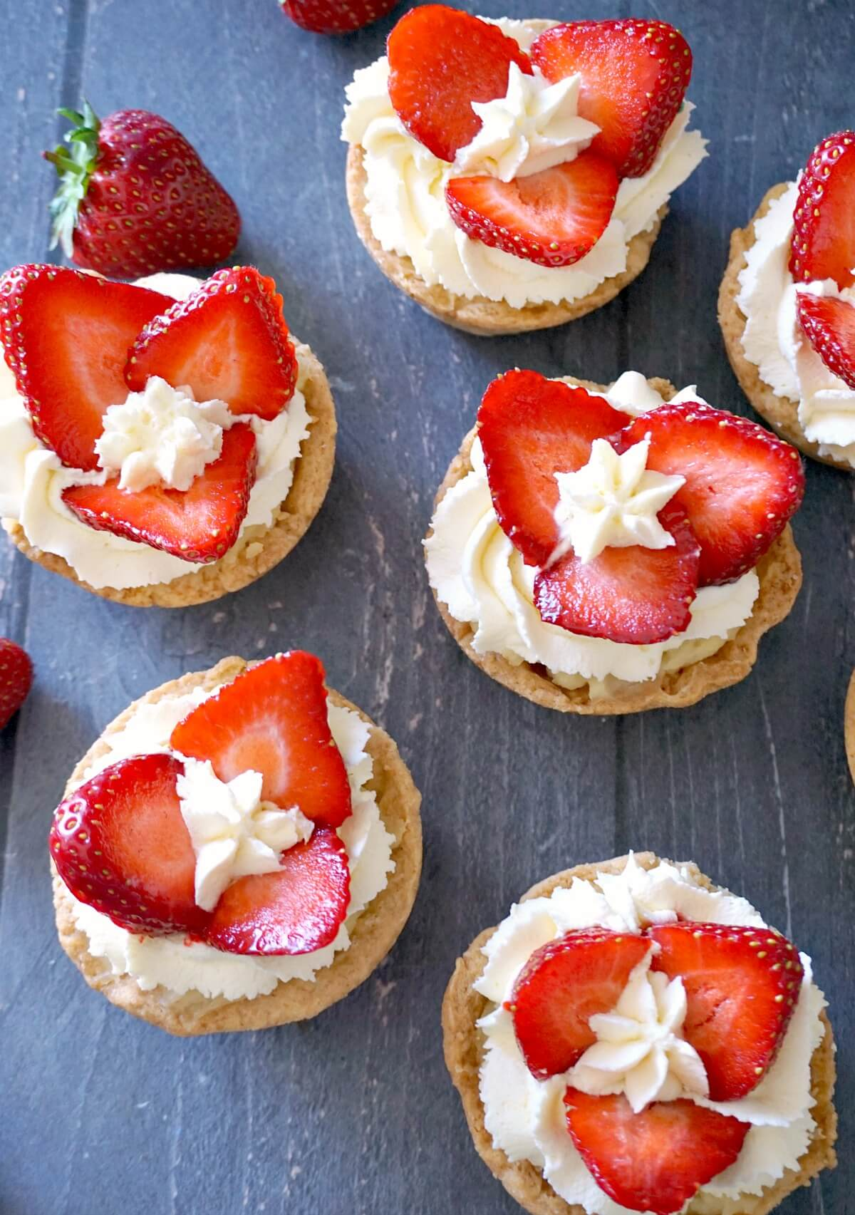 Overhead shoot of 6 strawberry and cream tartlets