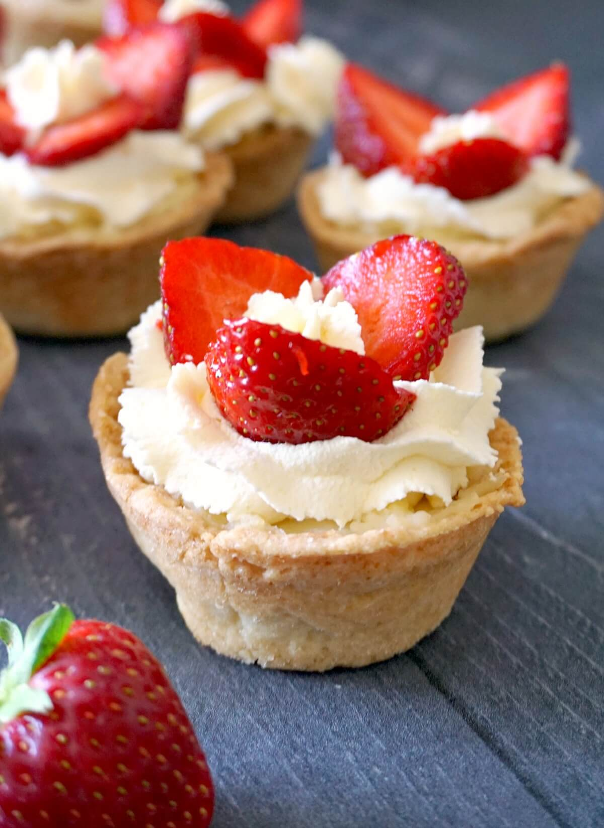 A tartlet with cream and 3 strawberry slices with other tartlets in the background