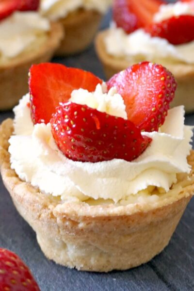 A mini tart with cream, custard and 3 strawberry slices with other tarts in the background
