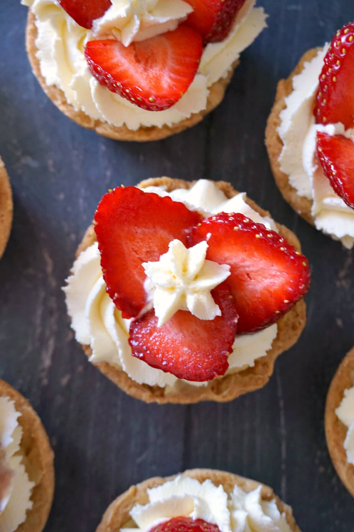 Overhead shoot of mini tarts with strawberry slices and cream
