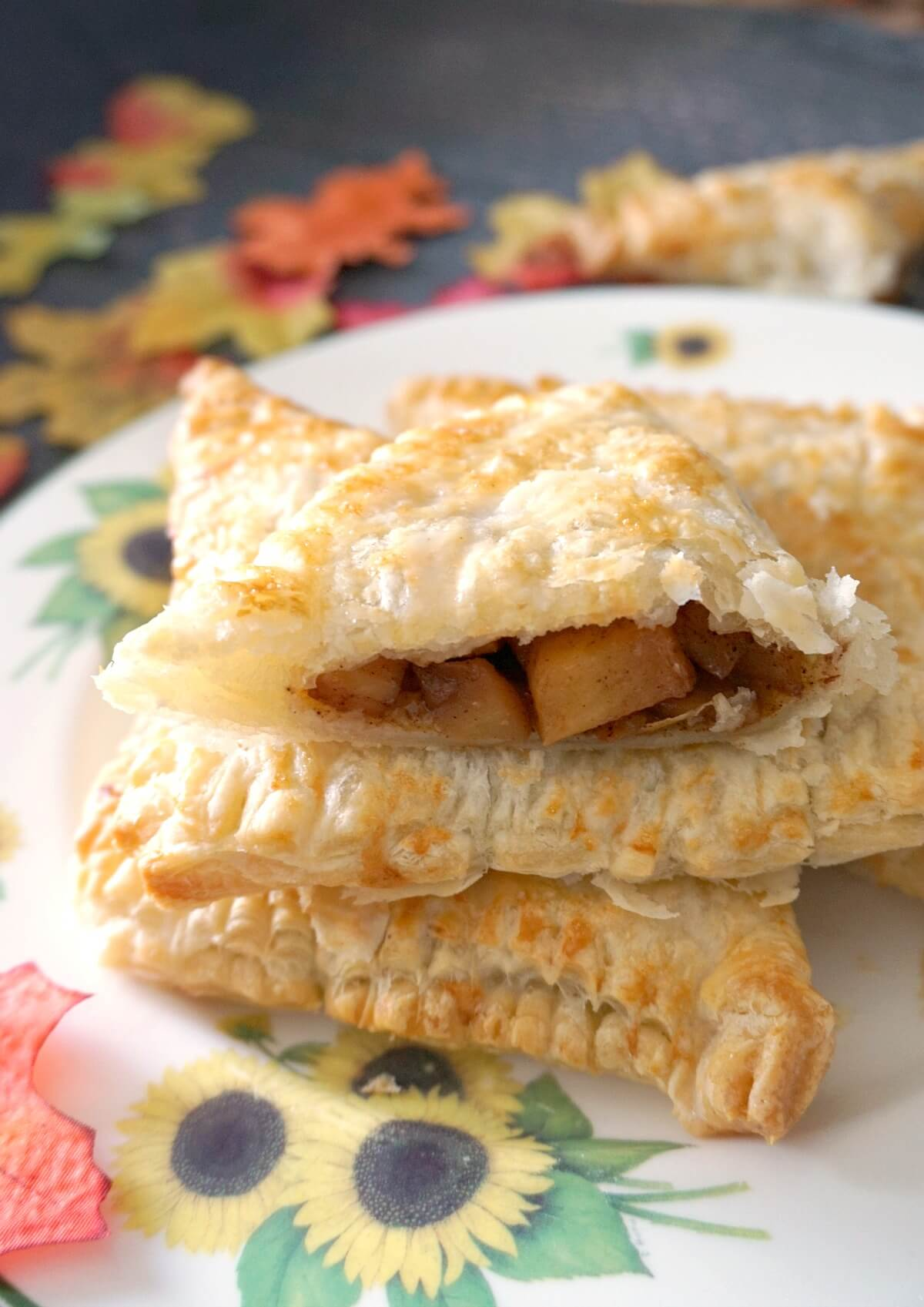 Half of an apple turnover on top of 2 whole ones