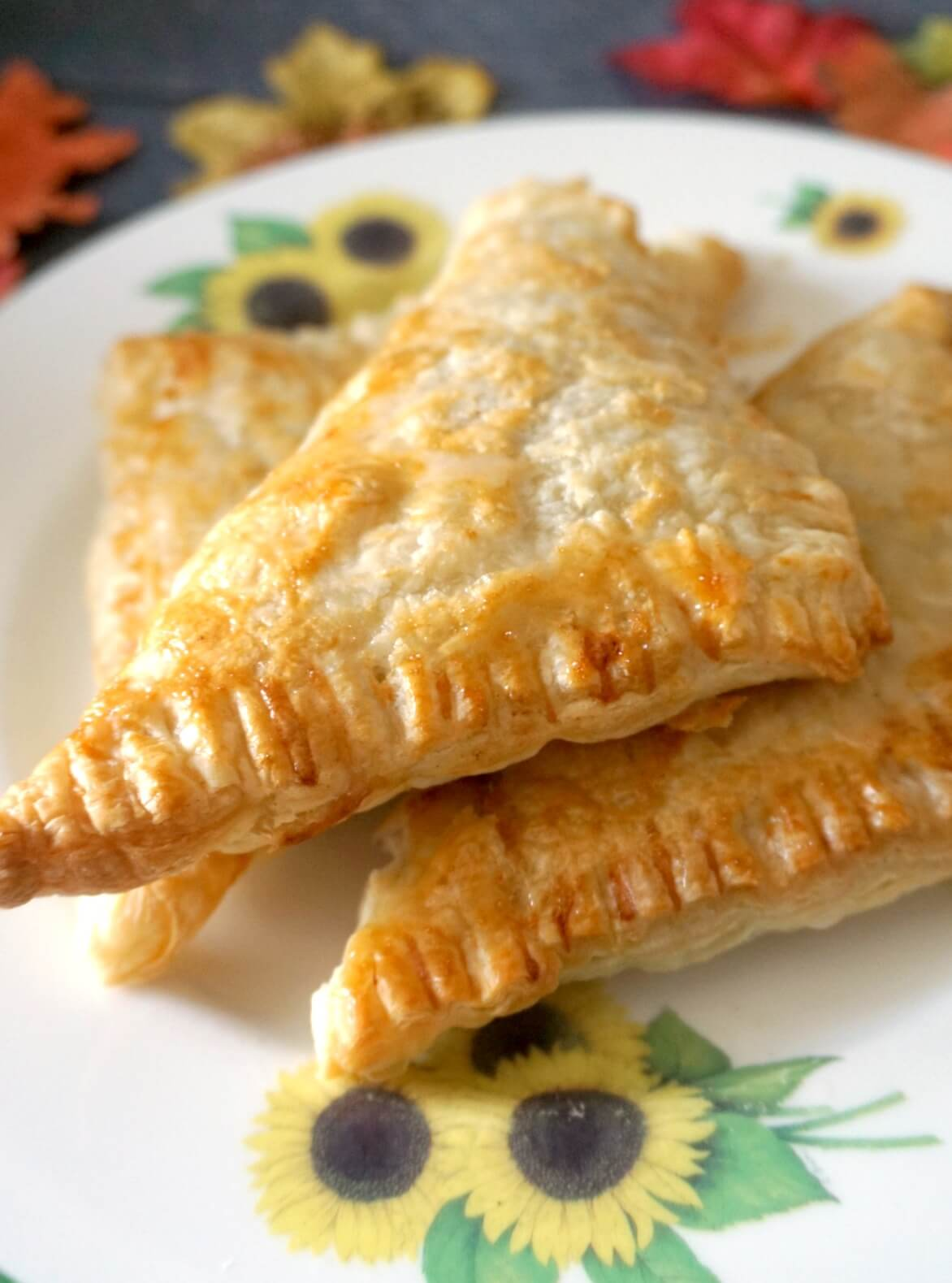 A stack of 3 apple turnovers on a large plate