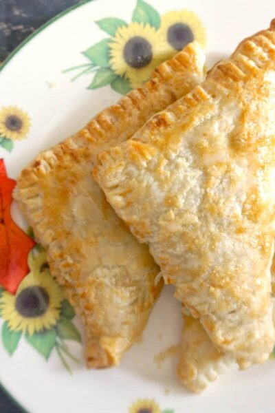 A stack of 3 apple turnovers on white plate with sunflowers