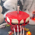 A bleeding cheesecake on a red cake stand with Halloween decorations around