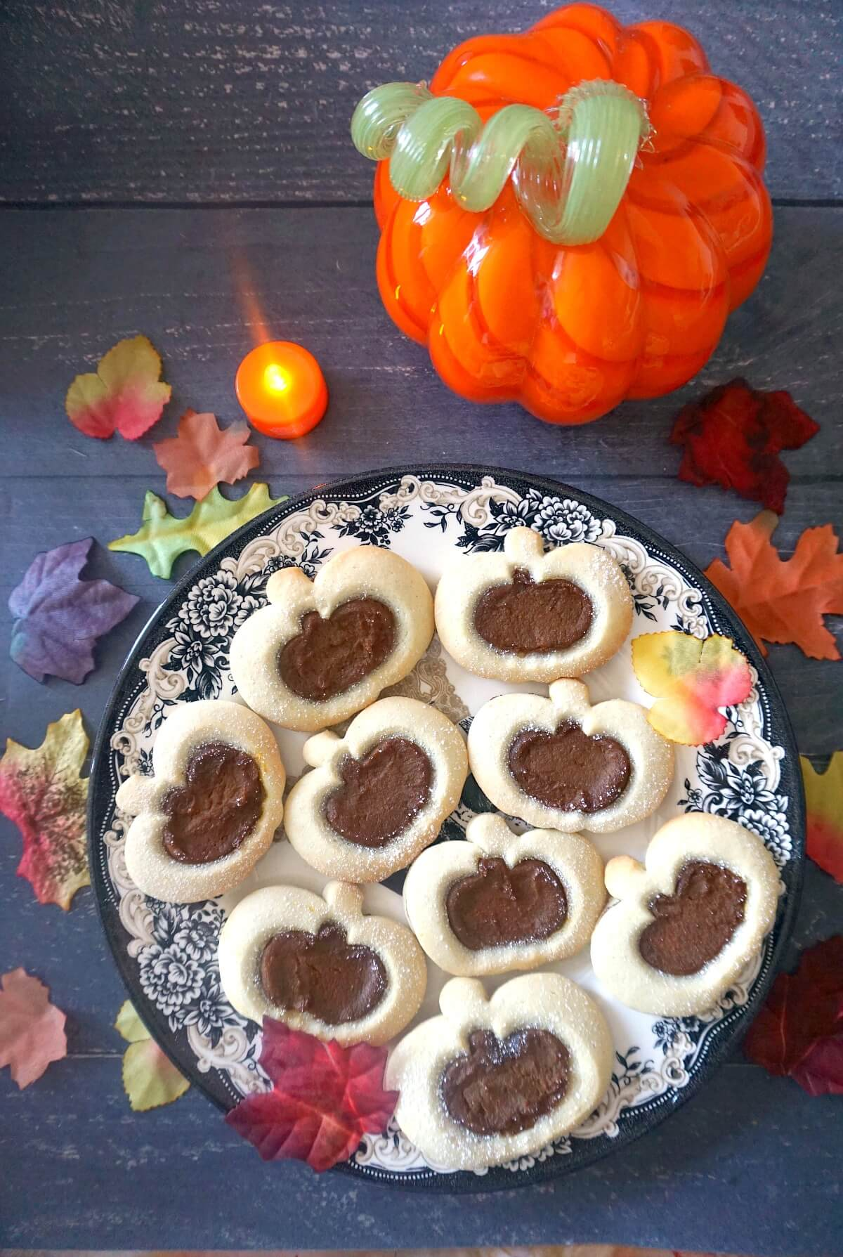 Overhead shoot of a plate with 9 pumpkin linzer cookies and fall decorations around