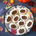 Overhead shoot of a plate with 9 linzer cookies in the shape of pumpkins