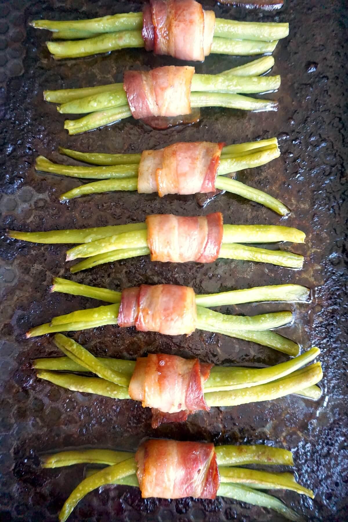 Overhead shoot of 5 green bean bundles in a baking tray