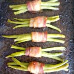 Overhead picture of 5 green bean bundles wrapped in bacon on a baking tray