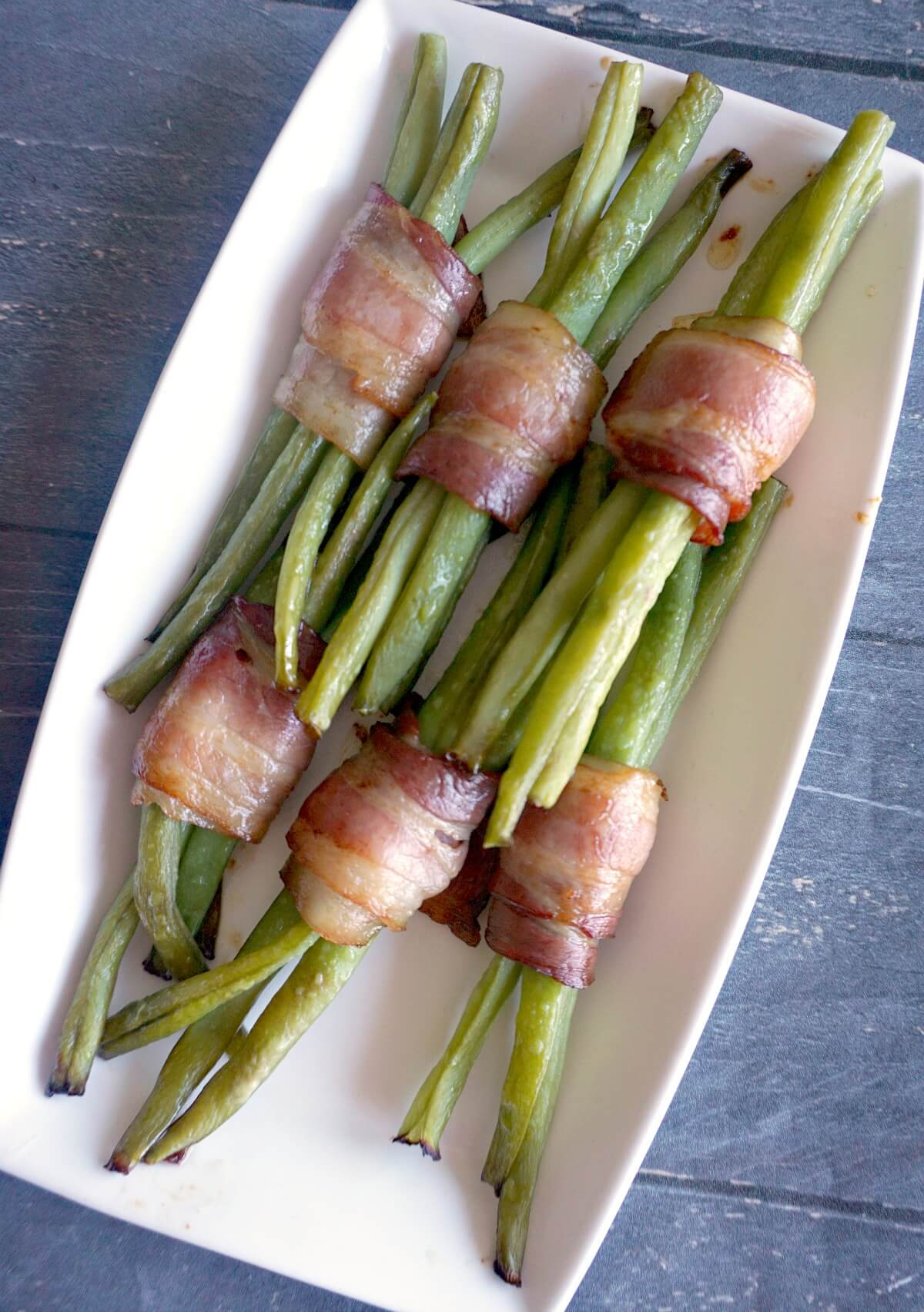 Overhead shoot of green bean parcels on a white rectangle plate
