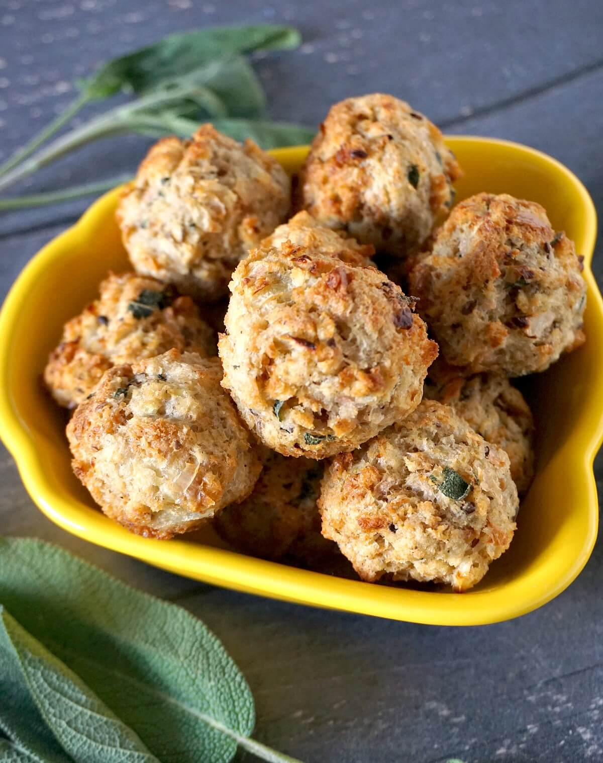 Sage and onion stuffing balls on a yellow appetizer bowl with fresh sage leaves around it