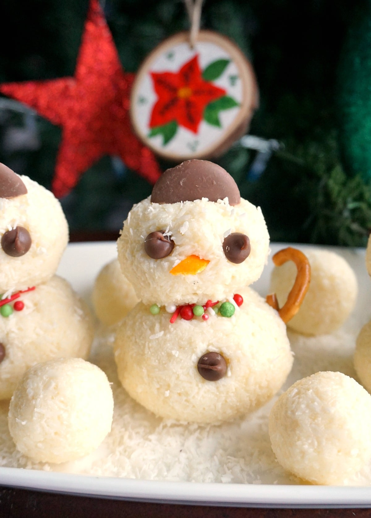 A snowman truffle and other truffles on a white rectangular plate