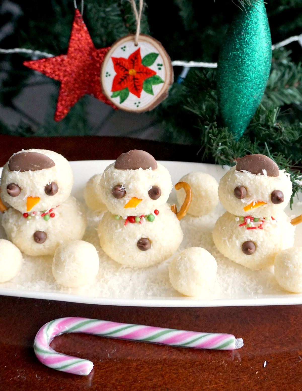 3 snowman truffles on a white rectangular plate with a Christmas tree in the background
