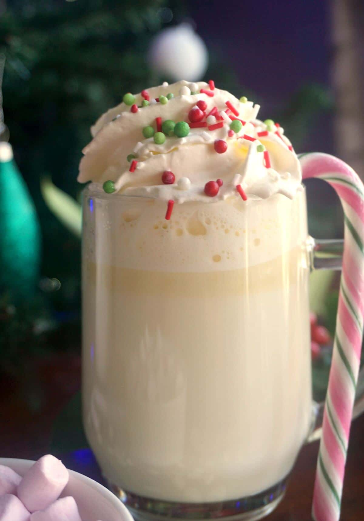 A glass of white hot chocolate with cream and sprinkles and a candy cane