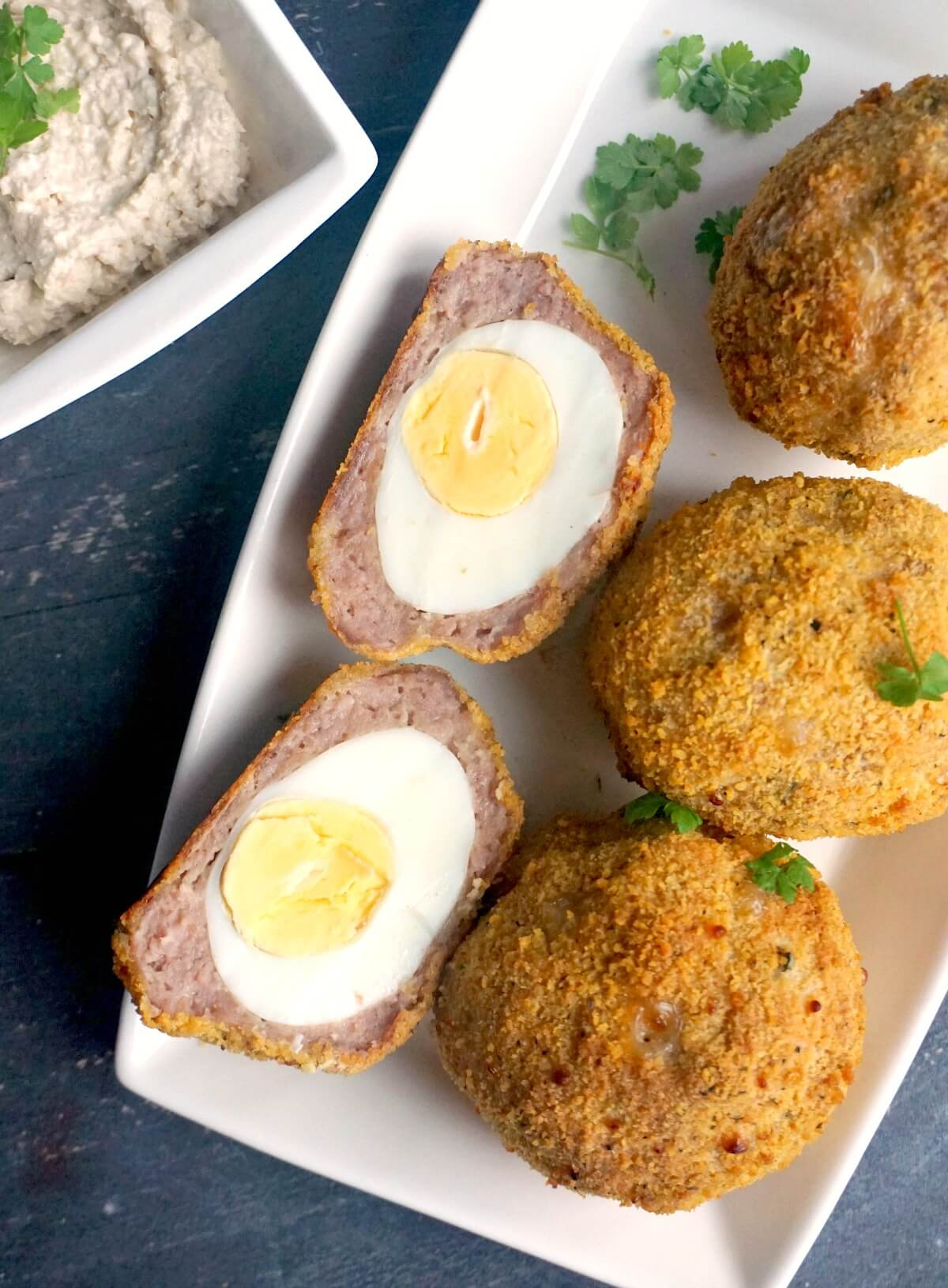 Overhead shoot of a white rectangle plate with 3 whole scotch eggs and 2 halves