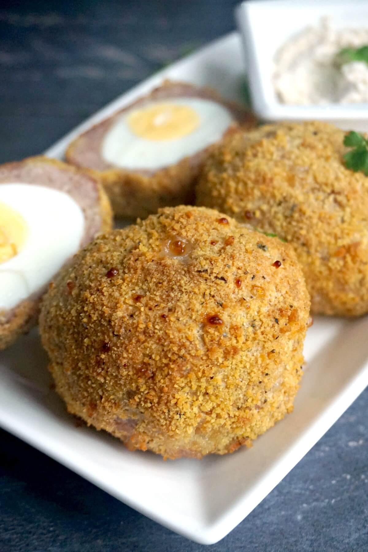 Close-up shoot of 2 whole scotch eggs and 2 halves in the background