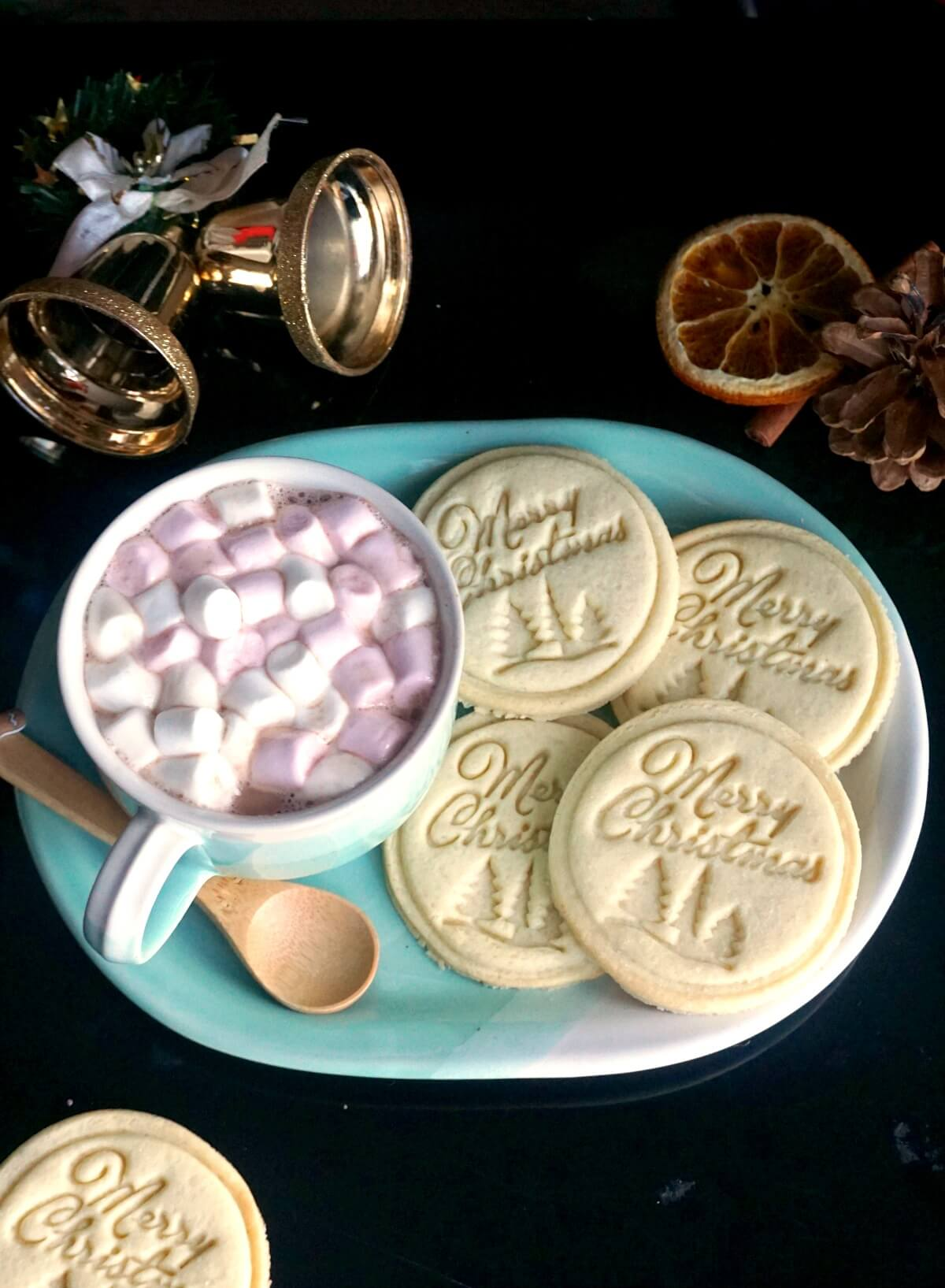 A blue plate with 4 stamped cookies and a cup of hot chocolate and marshmallows