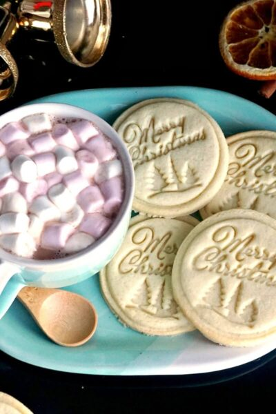 A blue plate with 4 Christmas stamped cookies and a mug of hot chocolate with marshmallows