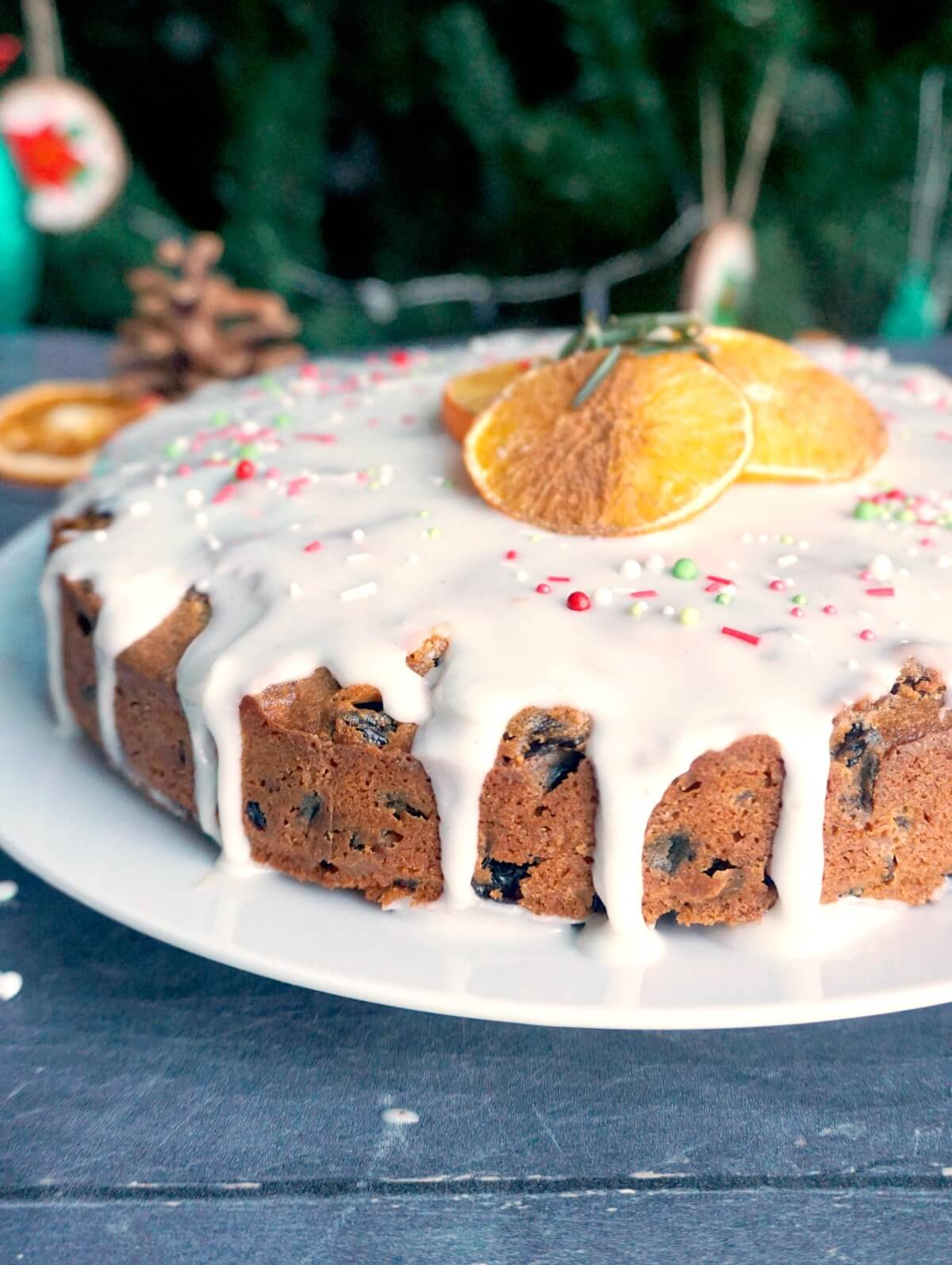 A Christmas cake with icing on top and dried orange slices