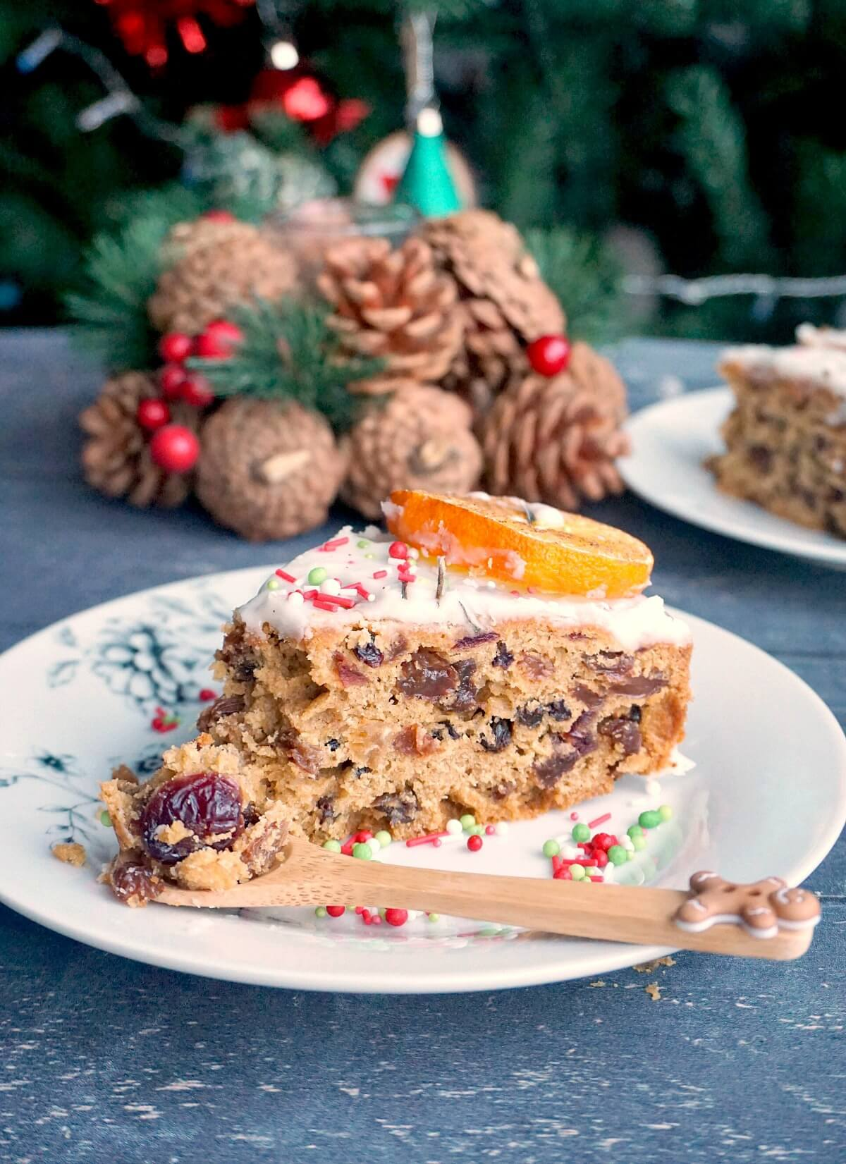 A slice of fruit cake and a wooden dessert spoon on a white plate with Christmas decorations in the background