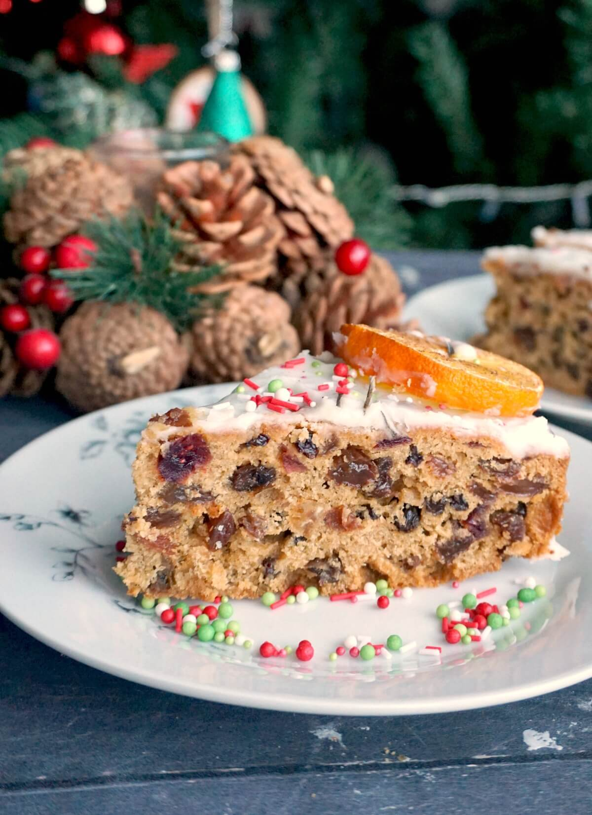 A slice of Christmas fruit cake on a white plate with Christmas decorations in the background