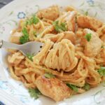A white plate with creamy linguine and cajun chicken