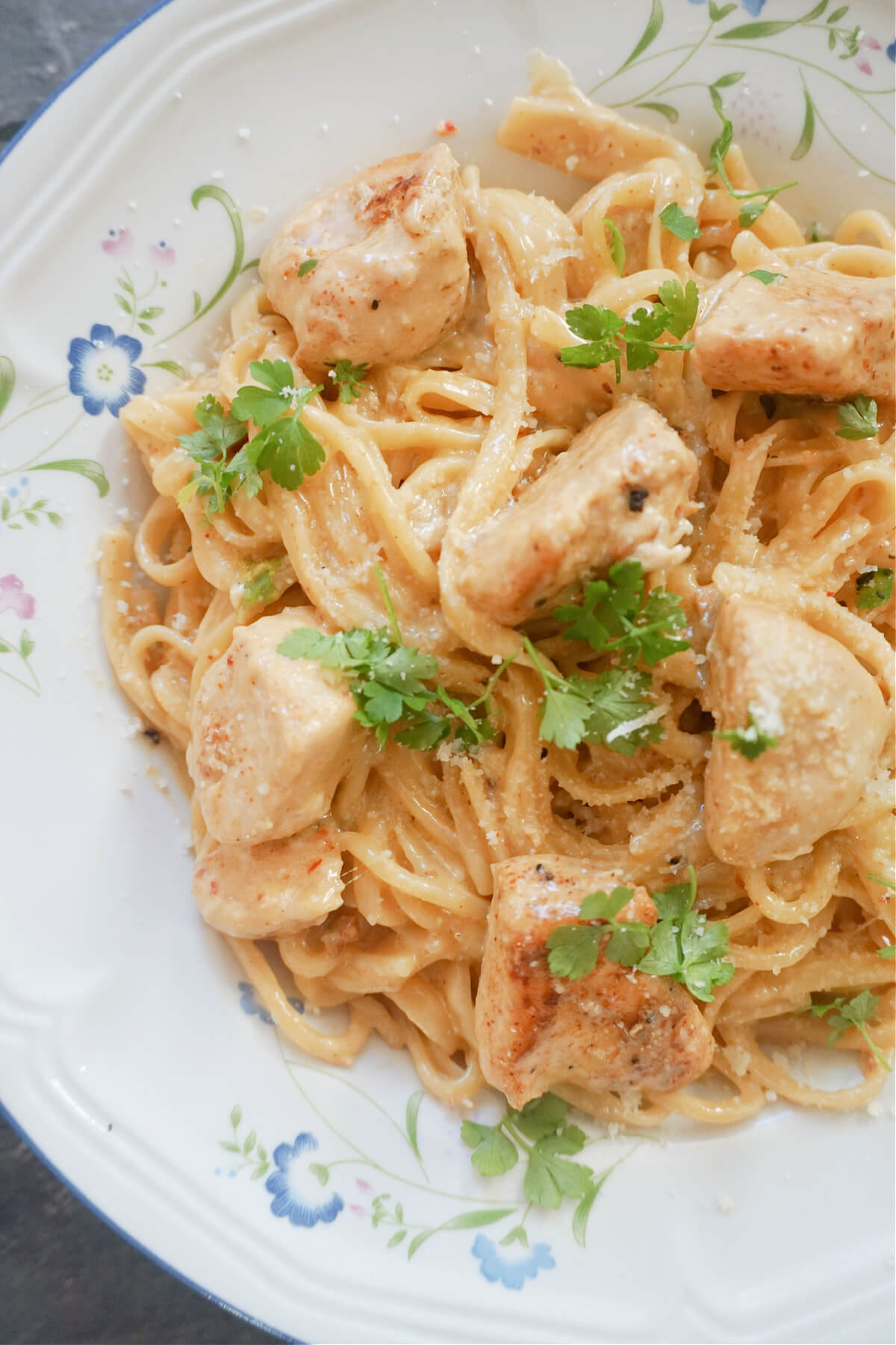 A white plate with spaghetti in creamy cajun chicken sauce