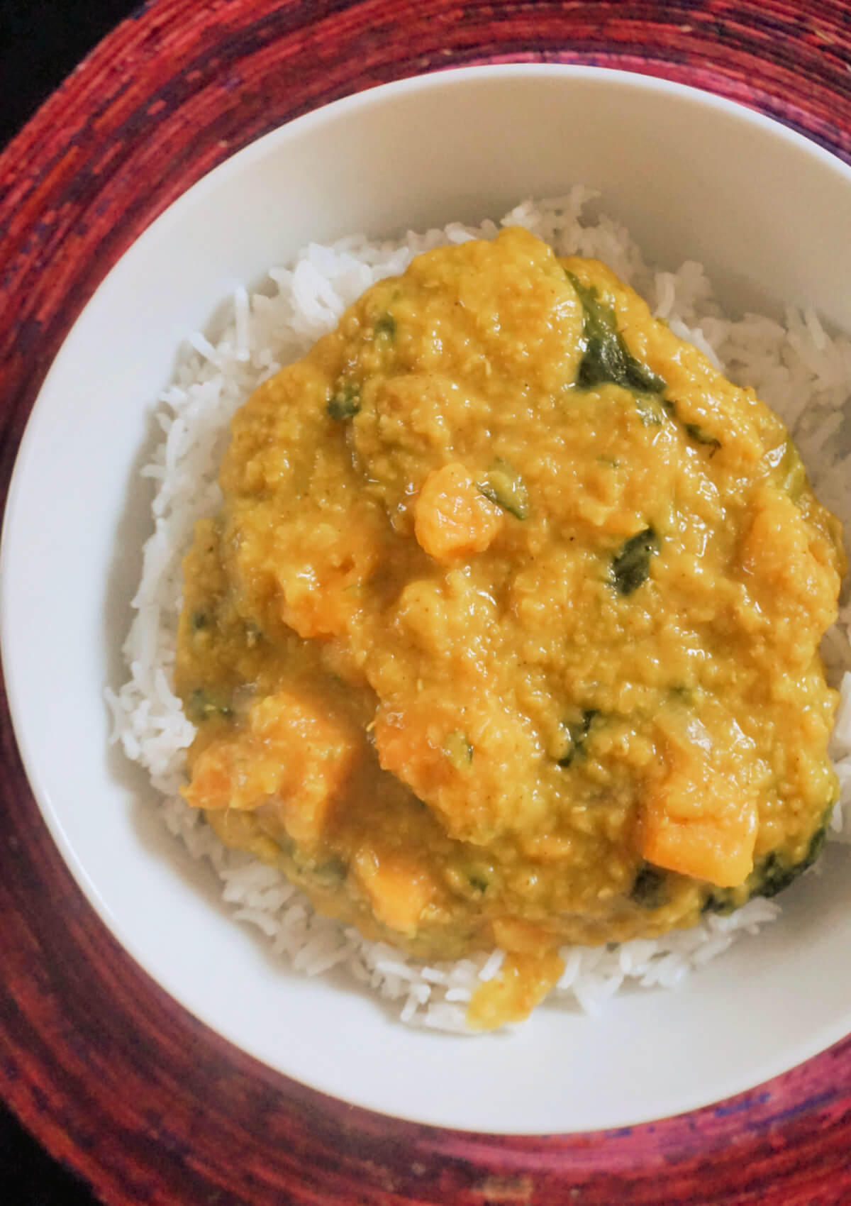 Overhead shot of a white plate with red lentil dahl over a bed of basmati rice
