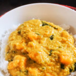 A white plate with rice and red lentil dhal