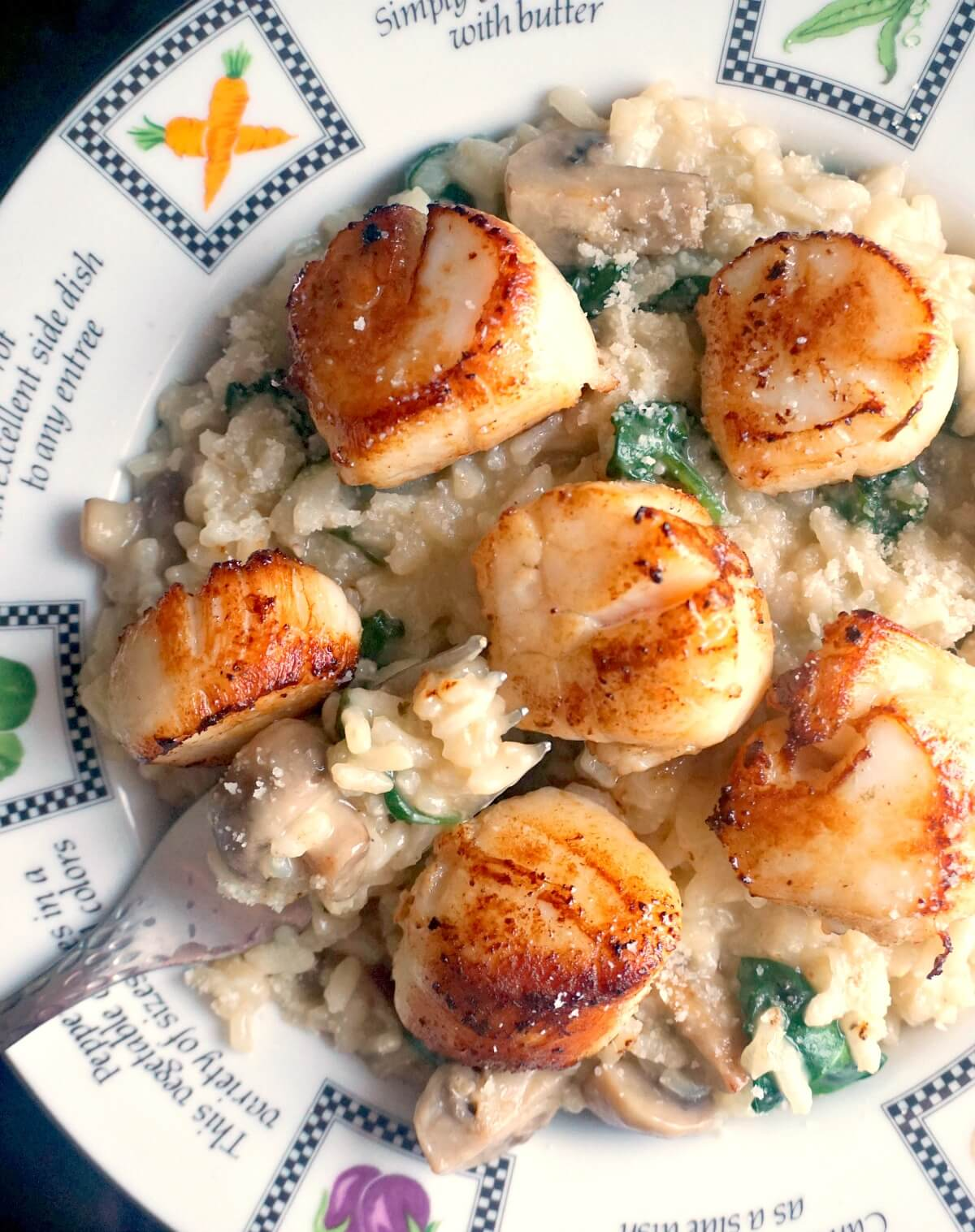 A plate with risotto topped with seared scallops