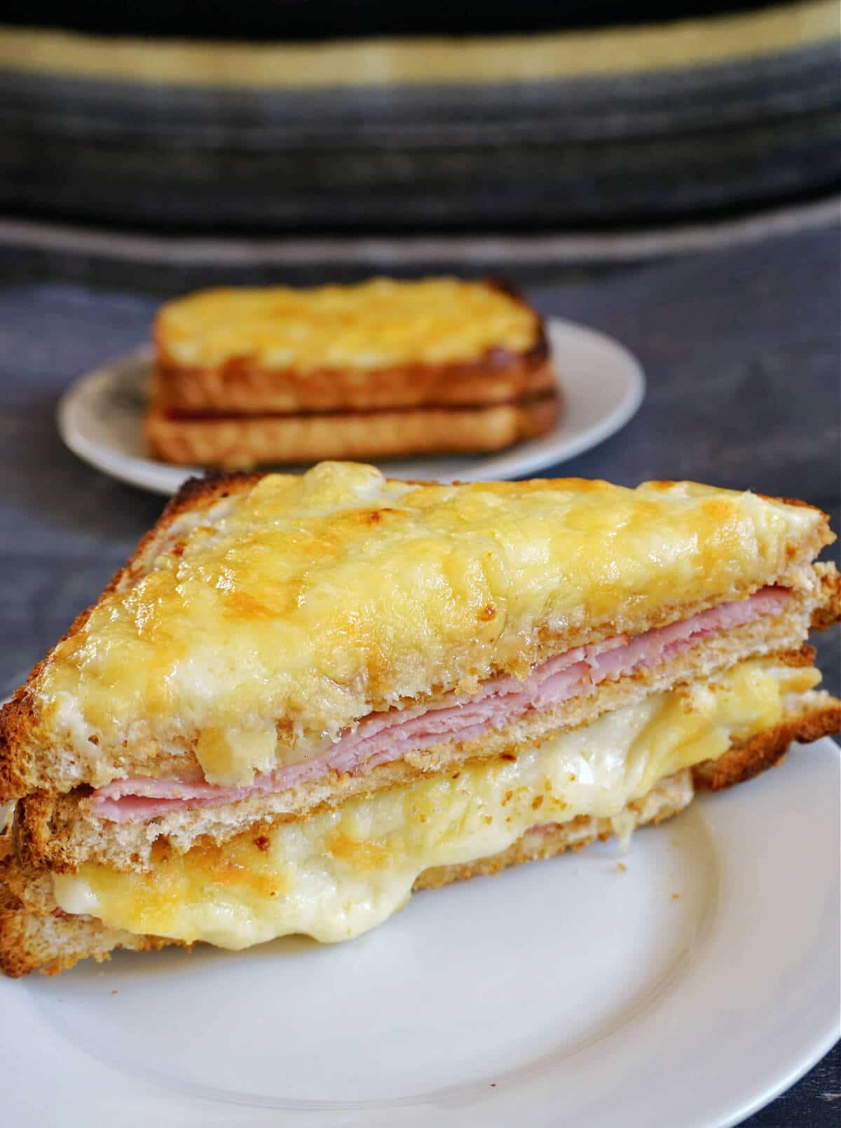 Half of a croque monsieur sandwich on a white plate with another plate with a whole sandwhich in the background