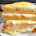 A stack of croque monsieur sandwiches cut in half on a white plate