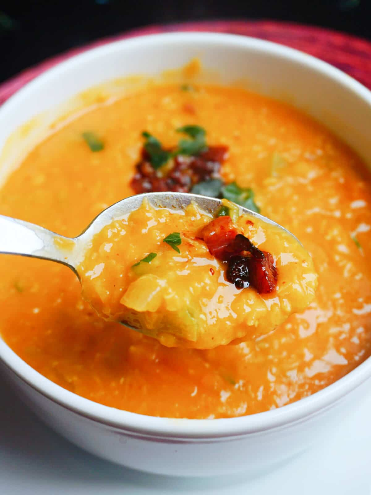 A spoonful of lentil and chorizo soup over a bowl of soup