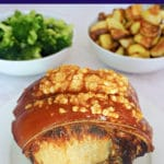 A roast pork with crackling on a white plate with 2 bowls of broccoli and roast potatoes in the background